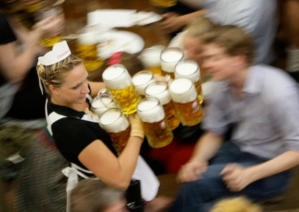 Waitress serves mugs of beer during 176th Oktoberfest in Munich