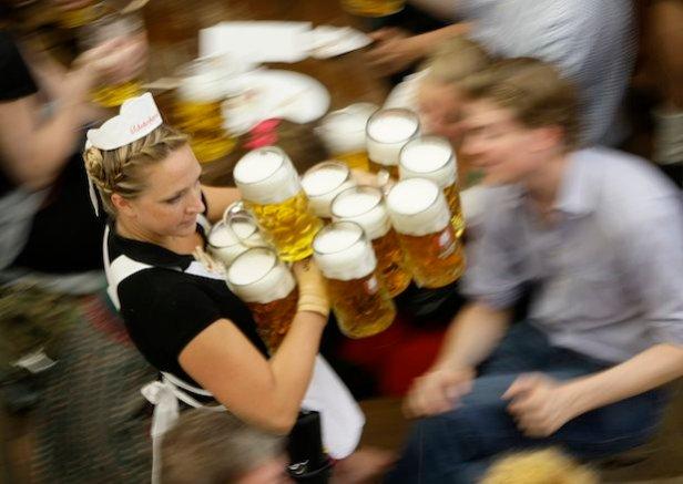 Waitress serves mugs of beer during 176th Oktoberfest in Munich