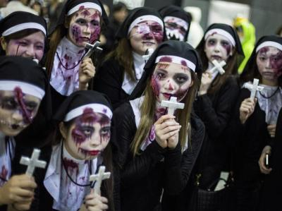 Women dressed as nuns pose for pictures during Halloween celebrations in the Shibuya district in Tokyo, Japan October 31, 2015.  REUTERS/Thomas Peter - RTX1U3FW